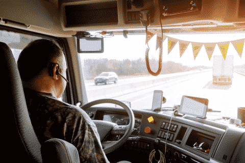 A trucker in the cab driving on the road.