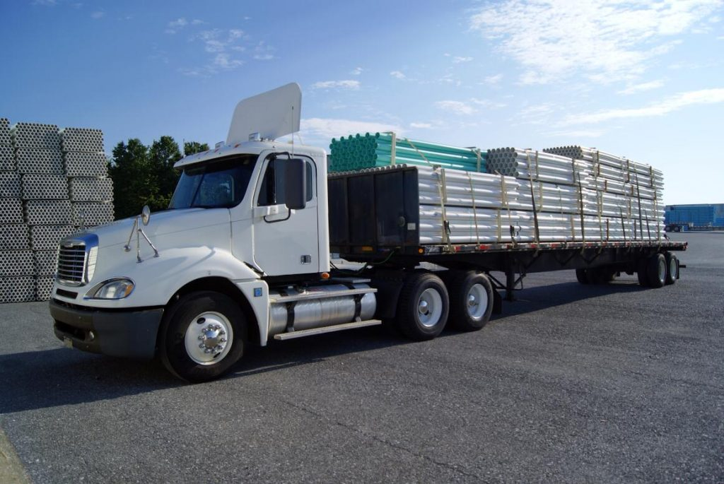 A flatbed truck on a loading dock.