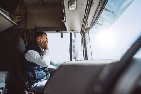 An OTR truck driver contacting dispatch while driving.