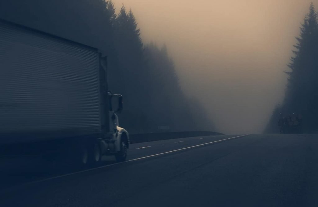 A truck driving on a highway during foggy weather