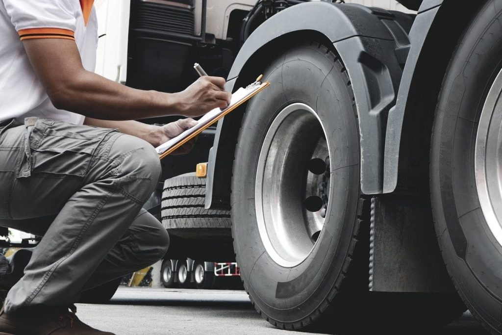 A driver inspecting the tires of a truck with a clipboard in their hand